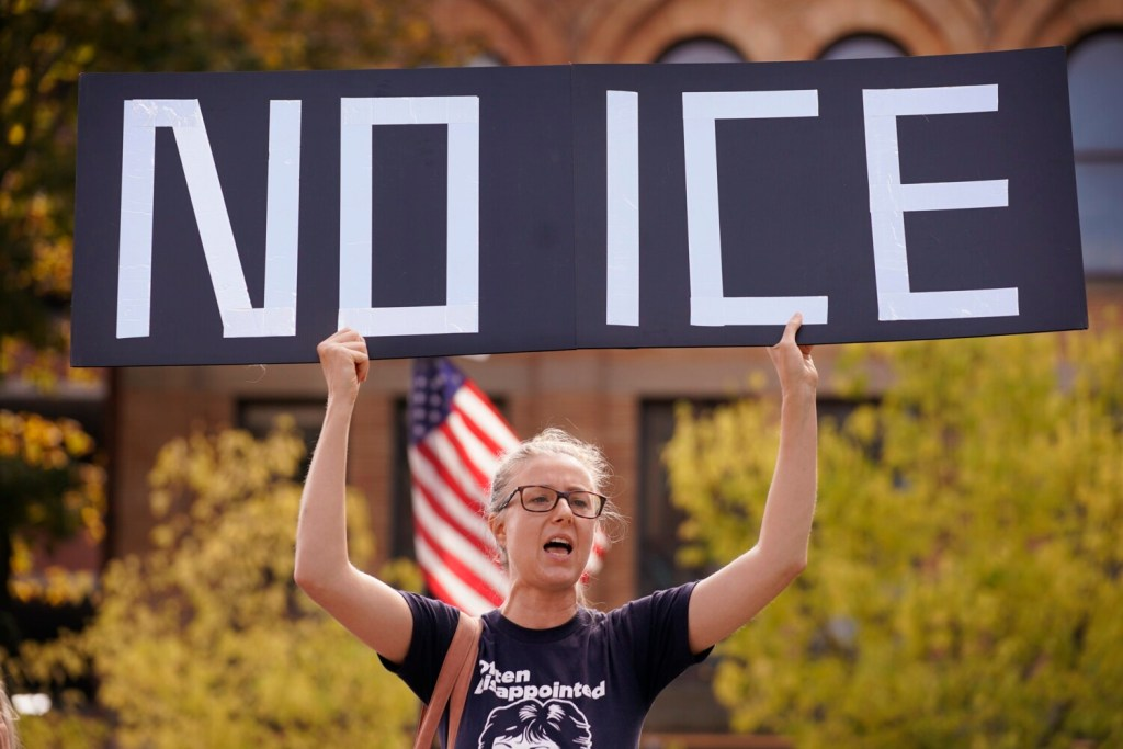 """Emily Qualey of Portland holds a """"No ICE"""" sign while chanting at a protest on Monday against an Immigration and Customs Enforcement office that will soon open at One City Center in Portland."""