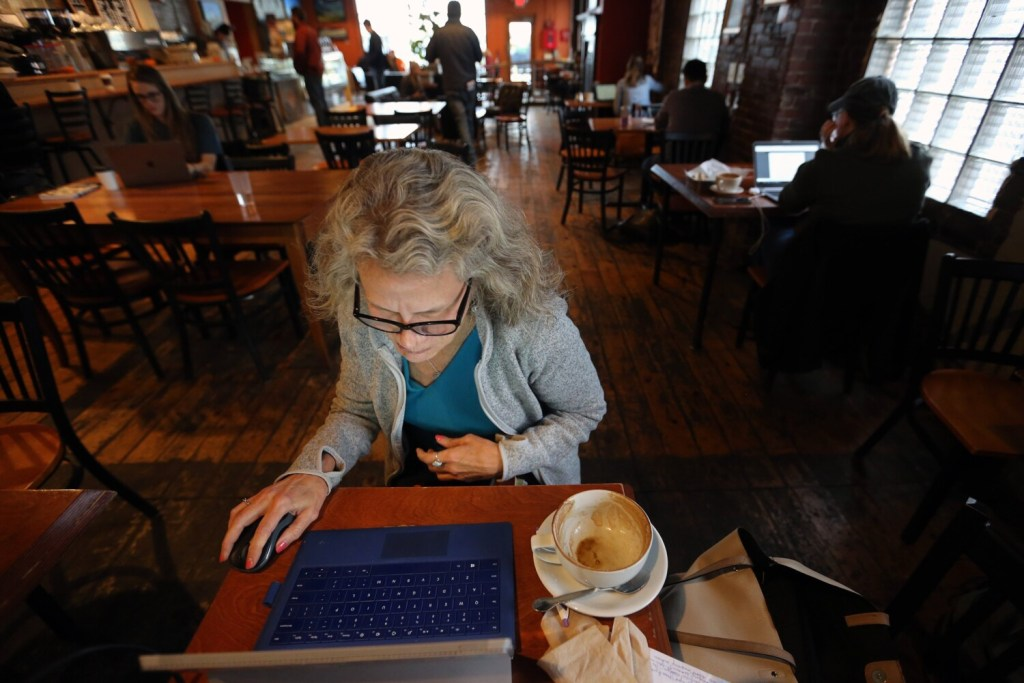 Marge Stockford of Portland works on her laptop Friday at Arabica Coffee after finishing a cup of cappuccino. Stockford chose the spot for its Internet connection because she had been without power since Thursday's early-morning nor'easter.