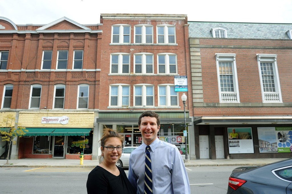 Tracy Nale, left, and brother Tom have purchased 99 Main St. in downtown Waterville. The property is pictured directly behind the pair on Tuesday. To the left of the couple are buildings they also own. At the right is The Center, the future home of the Paul J. Schupf Art Center.