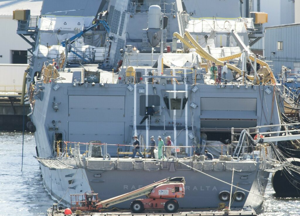 Workers walk across the aft deck of an Arleigh-Burke destroyer under construction at Bath Iron Works in 2016.