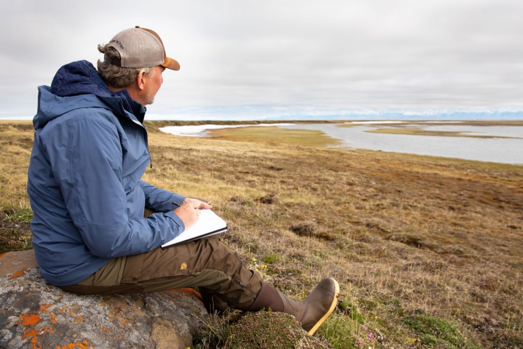 """Wildlife artist Michael Boardman of North Yarmouth sketches on the tundra in the Arctic National Wildlife Refuge, where he served as artist in residence for 10 days in June. """"It's so terrible to destroy this place in any way, shape or form,"""" he said."""