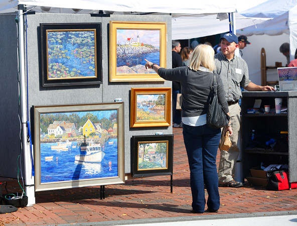 A visitor to last year's Fall Festival in Freeport examines artwork by Erik Minzer.