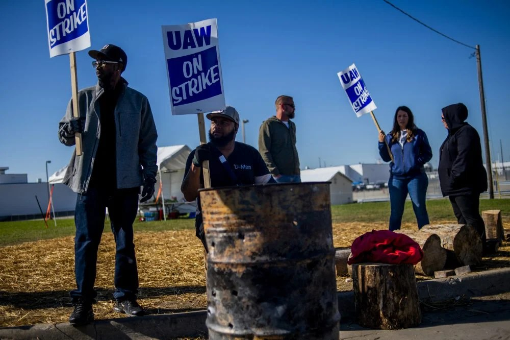 Detroit resident Jay Hawkins, left, and Flint resident Damien Moore picket outside of General Motors' Flint Paint Facility during the nationwide UAW strike against General Motors on Monday in Flint, Mich. An analysis estimates that as many as 100,000 workers – beyond the roughly 46,000 UAW strikers – have been laid off since the strike began.