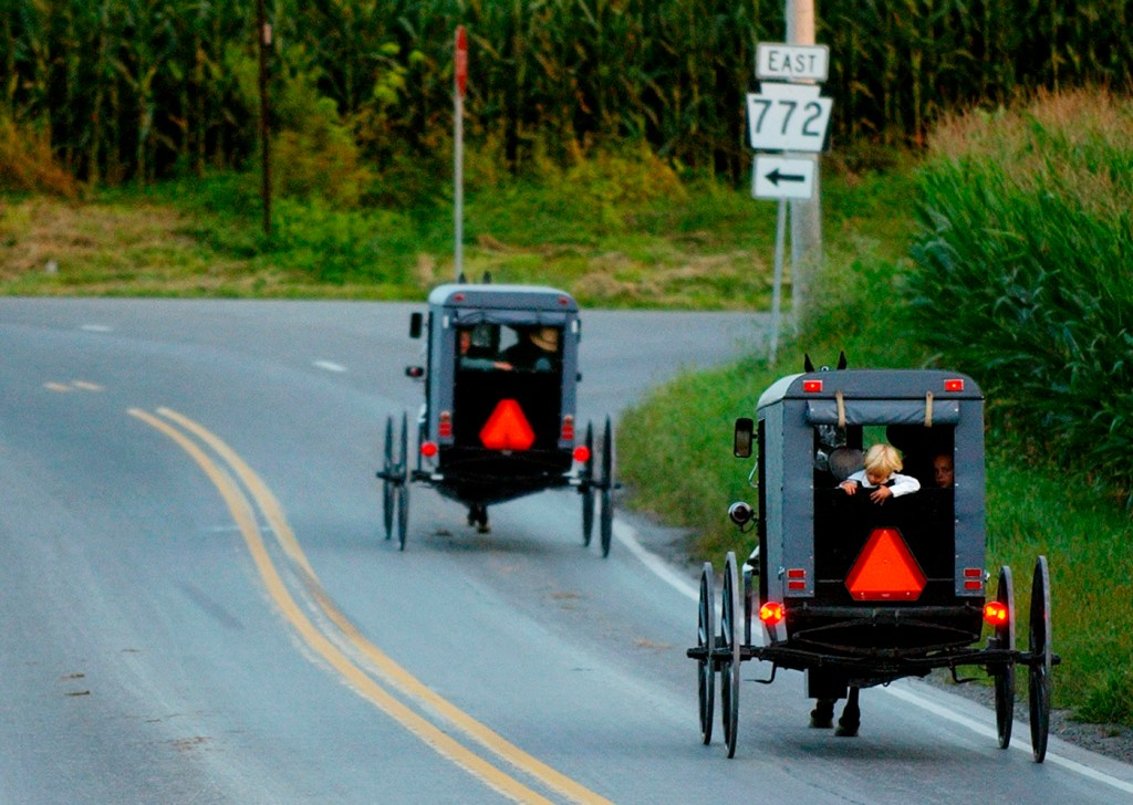 Amish hourse-drawn buggies trot along Pennsylvania  roads in 2003.