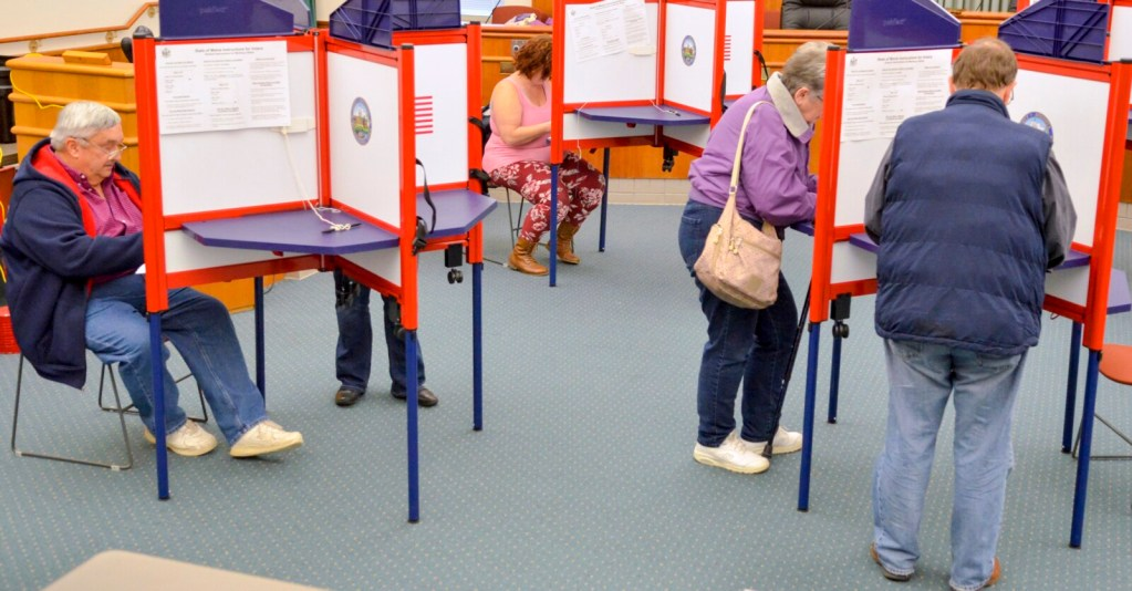 Voters sit and stand as they fill in their ballots Tuesday at Augusta City Center.