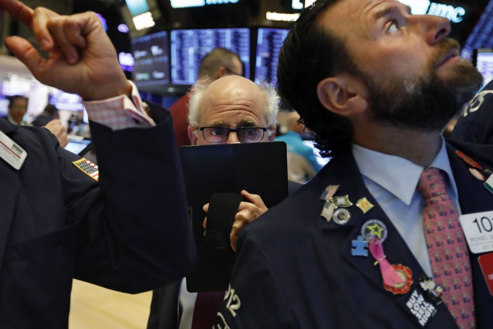 Trader Peter Tuchman, center, works on the floor of the New York Stock Exchange on Monday.