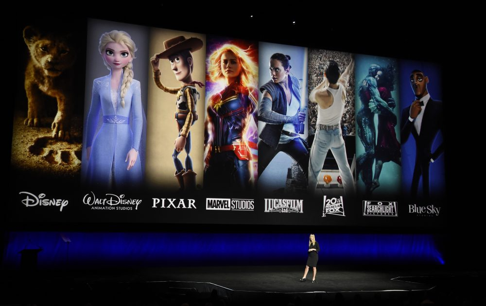 In this April 3, 2019, file photo characters from Disney and Fox movies are displayed behind Cathleen Taff, president of distribution, franchise management, business and audience insight for Walt Disney Studios during the Walt Disney Studios Motion Pictures presentation at CinemaCon 2019, the official convention of the National Association of Theatre Owners (NATO) at Caesars Palace in Las Vegas. On Tuesday, Disney Plus launched its streaming service.