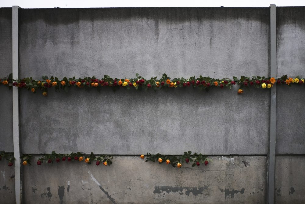 Flowers stuck in remains of the Berlin Wall during a commemoration ceremony Saturday to celebrate the 30th anniversary of the fall of the Berlin Wall at the Wall memorial side at Bernauer Strasse in Berlin.
