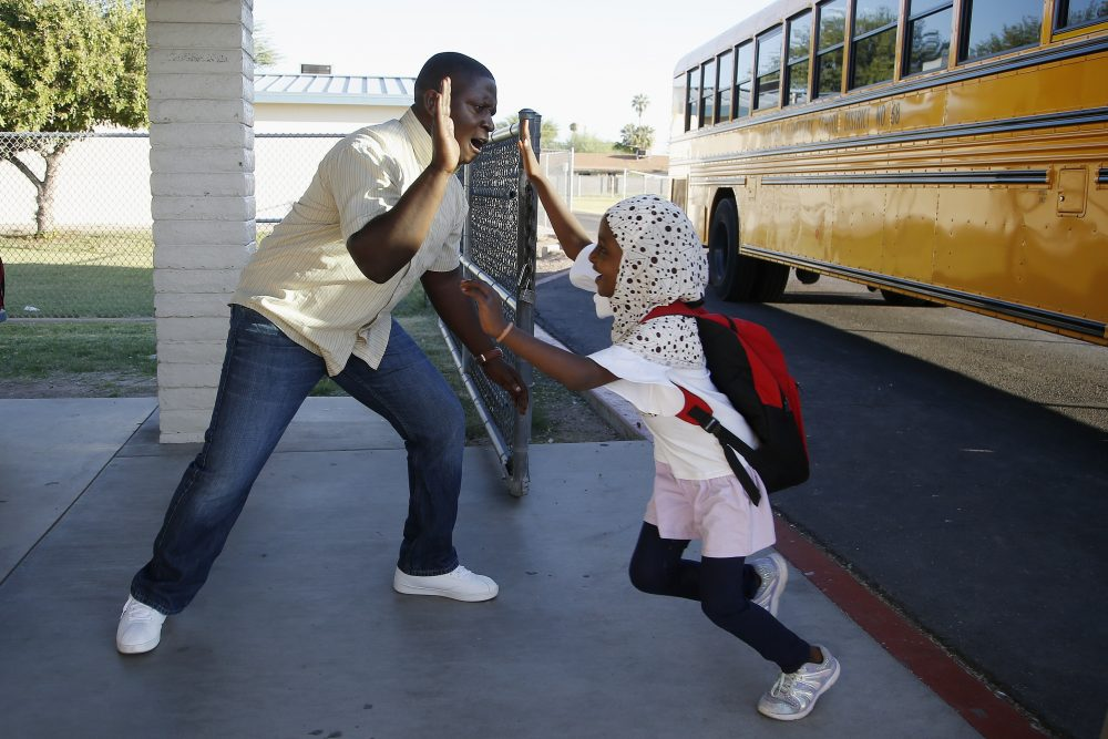 Samuel Lavi, left, a Congolese native who is a teaching assistant and family engagement liaison, greets first-grader Kediga Ahmed as she arrives at the Valencia Newcomer School in Phoenix.   (AP Photo/Ross D. Franklin)