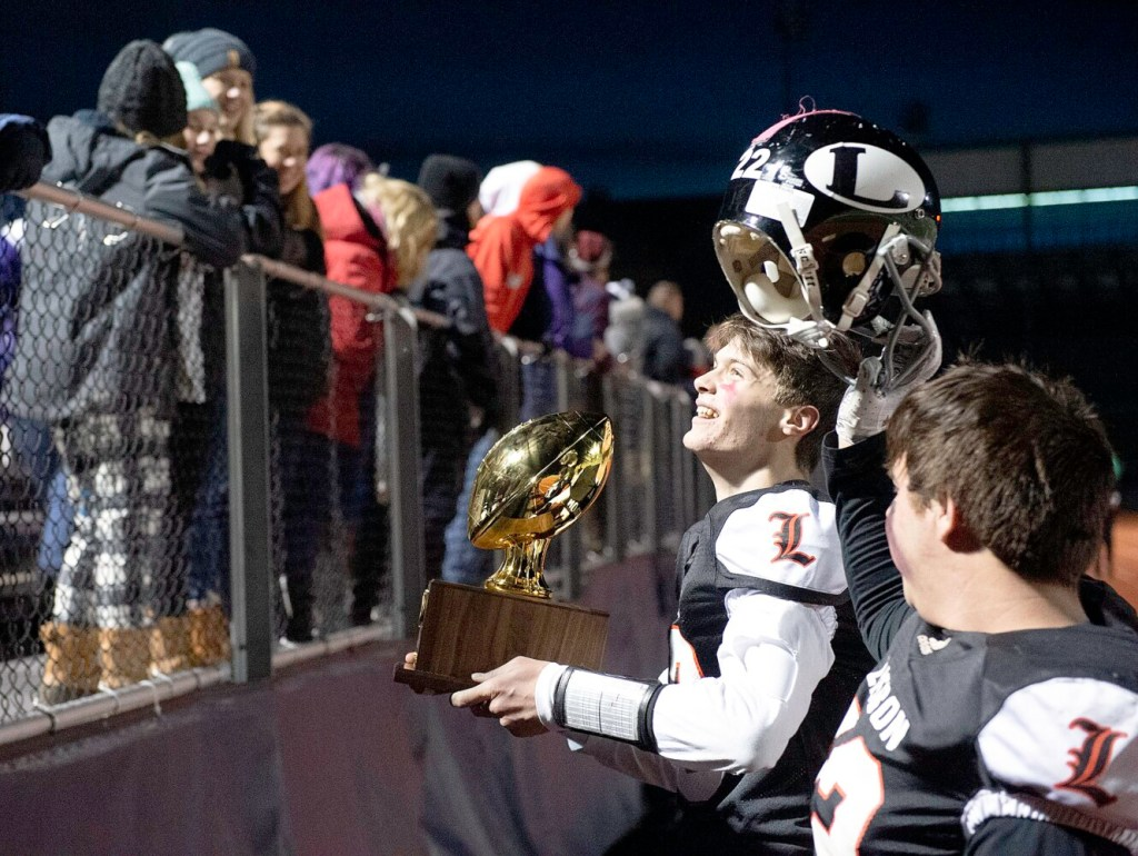 Lisbon/St. Dominic quarterback Seth Leeman shows the crowd the Gold Ball after the Greyhounds beat Bucksport 28-8 to win the Class D title on Saturday at Fitzpatrick Stadium in Portland.