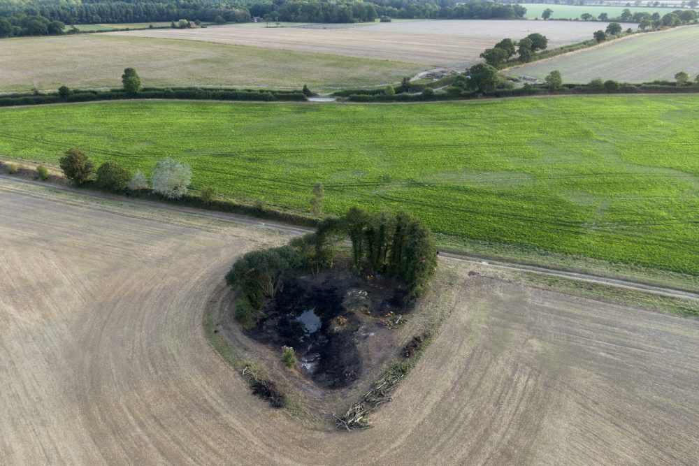 A wetland is surrounded by farmland near Hindolveston, Dereham, eastern England, shown on Sept. 13. Around the world, efforts are being made to reclaim wetlands that have been filled in to plant crops or meet other human needs.