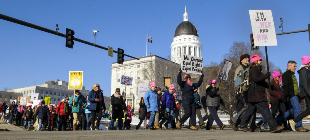 Marchers cross State Street in front of the Maine State House at the beginning of the Maine Women's March 2.0: Power to the Polls in January in Augusta. They started with speakers in the plaza between Cross State Office Building and State House before taking a lap around Capital Park.