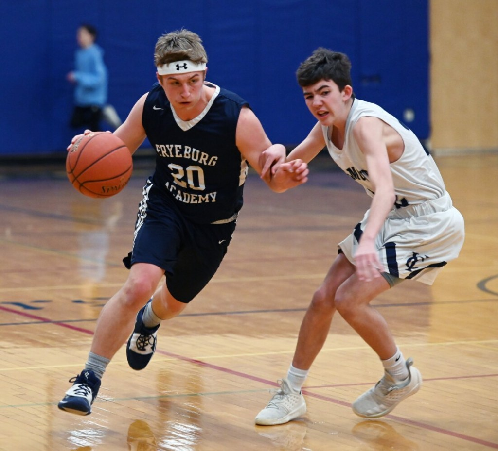 Fryeburg's Calvin Southwick dribbles up court while being defended by Yarmouth's Matt Waeldner on Friday in Yarmouth. Southwick made a 3-pointer to force overtime and the Raiders won 58-55.