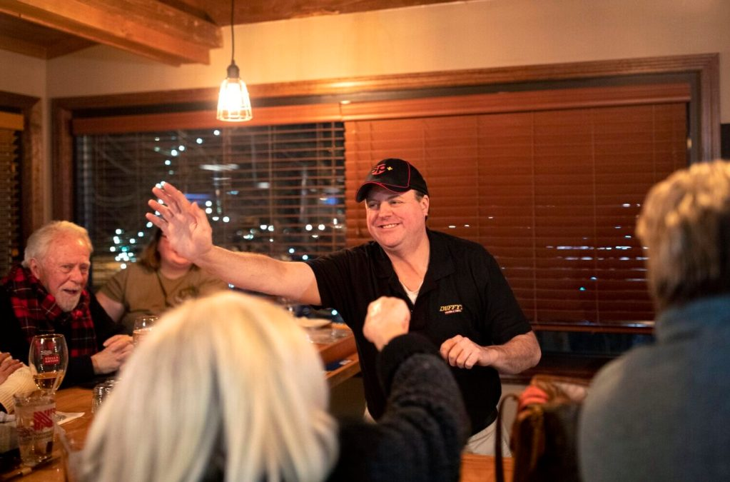 """Dennis Coffey walks along the bar high-fiving patrons at Duffy's Tavern & Grill, who watched him repeat as champion in Monday night's """"Jeopardy!"""" show."""