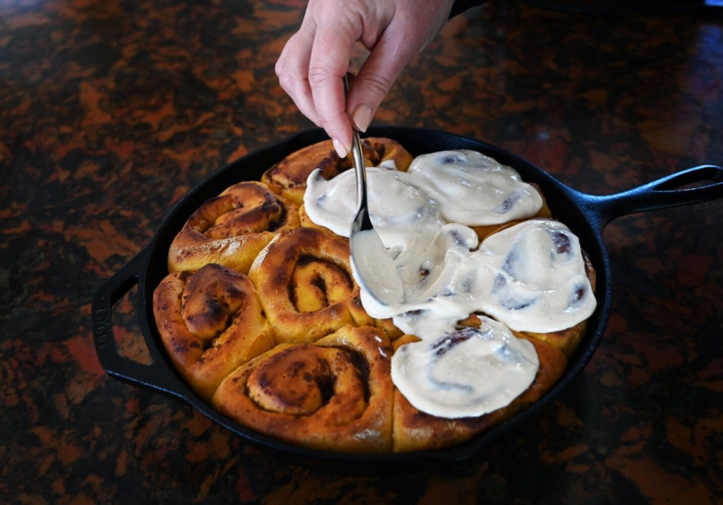 Sweet potato cinnamon buns get a cream cheese frosting sweetened with maple syrup.
