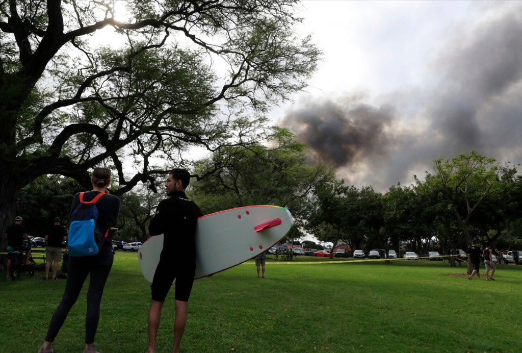Kai Ohashi, right, and Lucy Taylor observe billowing smoke from a house fire after a shooting and domestic incident at a residence on Sunday in Honolulu. Witnesses say at least two police officers were shot and two civilians were injured.