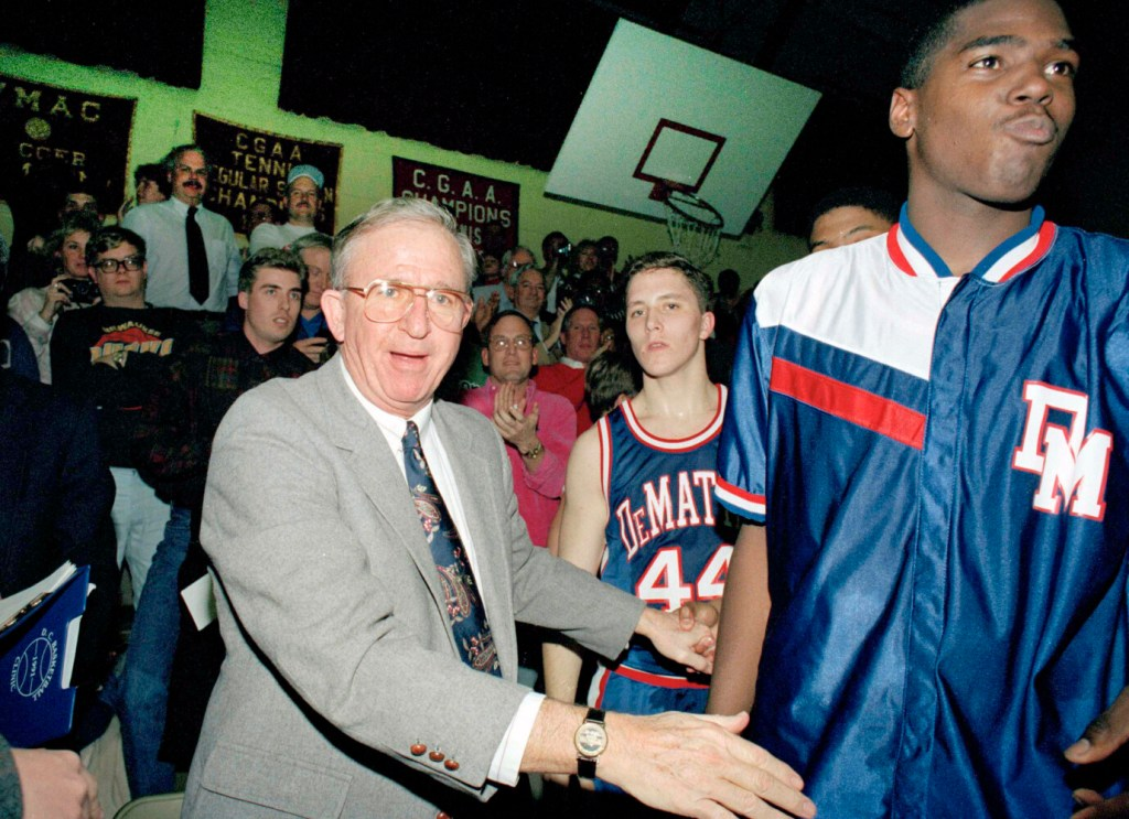 """FILE - In this Jan. 22, 1993, file photo, DeMatha High School basketball coach Morgan Wootten walks from the bench after his 1,000th victory, in Alexandria, Va. Next to Wootten are DeMatha players Tim Strachan (44) and Steve Napper, right. Morgan Wootten, a Hall of Fame basketball coach who built DeMatha High School into a national powerhouse and mentored several future NBA stars during a career that spanned parts of six decades, has died.  He was 88. The school announced his death on Twitter, writing, """"The Wootten Family is saddened to share the news that their loving husband and father Morgan Wootten passed away"""" on Tuesday night, Jan. 21, 2020. (AP Photos/Ted Mathias, File)"""