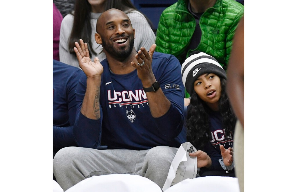 Kobe Bryant and his daughter Gianna watch the first half of an NCAA college basketball game between Connecticut and Houston on March 2, 2019.
