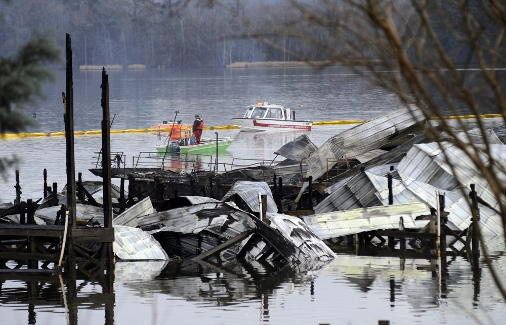 People on boats patrol near the charred remains of a dock following a fatal fire at a Tennessee River marina in Scottsboro, Ala., on Monday. Authorities said the explosive fire was reported overnight while people were sleeping on boats tied up at the structure.