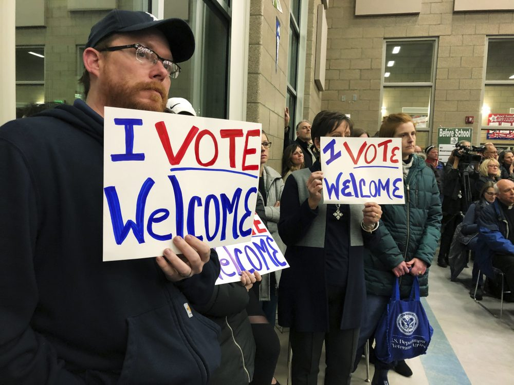 Residents in support of continued refugee resettlement hold signs at a meeting in Bismarck, N.D., on Jan. 15. Rural Maine counties would do well to welcome refugees, too. James MacPherson/Associated Press