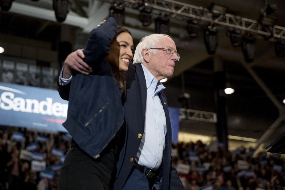 Democratic presidential candidate Sen. Bernie Sanders, I-Vt., accompanied by Rep. Alexandria Ocasio-Cortez, D-N.Y., takes the stage at a campaign stop at the Whittemore Center Arena at the University of New Hampshire on Monday in Durham, N.H. Primary voters cast their ballots Tuesday.