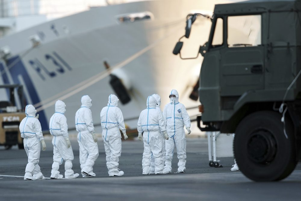 Officials with protective suits prepare to work around the quarantined cruise ship Diamond Princess in the Yokohama port on Monday in Yokohama, Japan. Japan's health ministry said Monday that dozens of people on the quarantined cruise ship have tested positive for a new coronavirus virus.