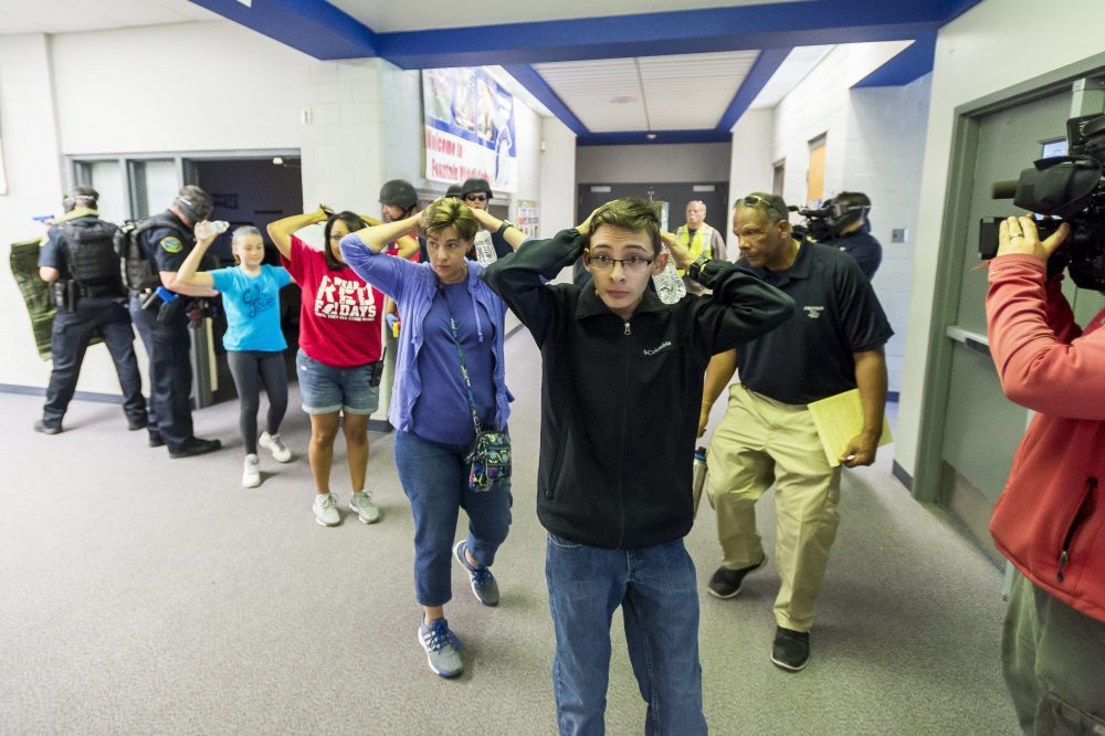 Students are led out of school as members of the Fountain Police Department take part in an Active Shooter Response Training exercise at Fountain Middle School in Fountain, Colo., in 2017. The nation's two largest teachers unions want schools to revise or eliminate active shooter drills, asserting they can harm students' mental health.