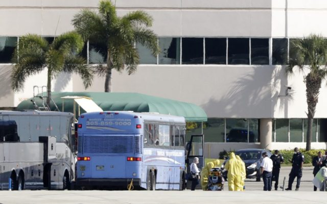 Paramedics wearing yellow protective suits to prevent the spread of the coronavirus stand at the ready as passengers who came off the cruise ship Rotterdam get off a bus to board a charter plane at Fort Lauderdale–Hollywood International Airport on Friday in Fort Lauderdale, Fla.