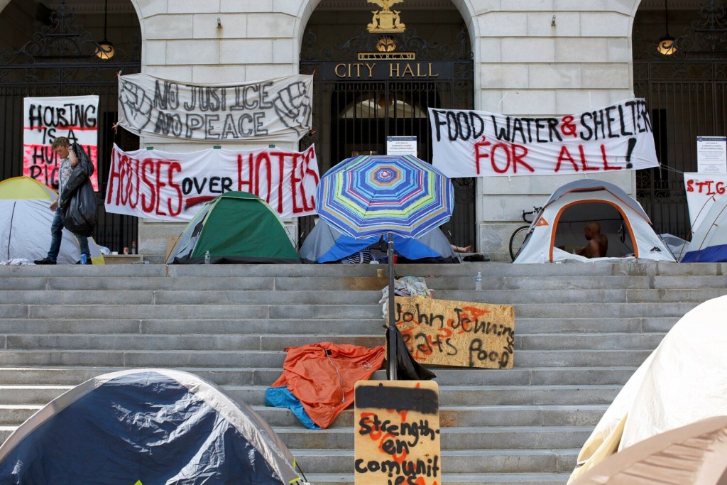 """Tents and protest signs line the top of the steps at Portland City Hall as the so-called """"sleep out"""" enters another night."""