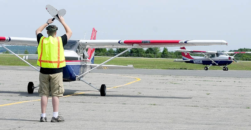 DIRECTING TRAFFIC: Civil Air Patrol cadet Avery Spear directs a plane's crew into position on Tuesday at the Augusta State Airport.