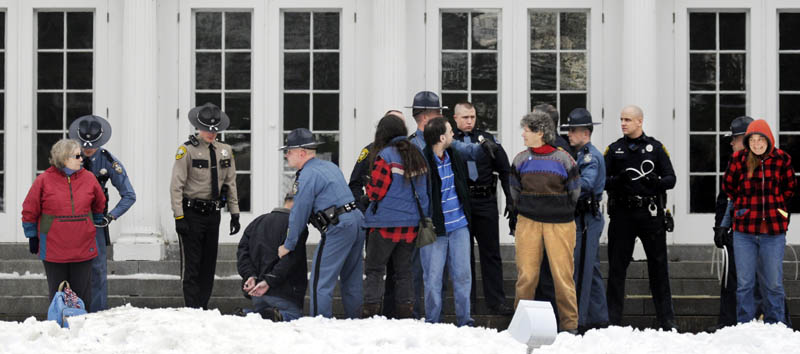 Protesters are arrested Sunday on the lawn of the Blaine House during a rally by Occupy Augusta. Police say nine people were charged with criminal trespass and failure to disperse after refusing to leave the lawn of the governor's mansion.