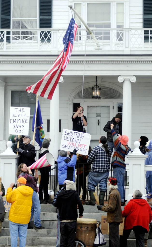 """Protesters hoist a flag embroidered with """"99%,"""" along with the American flag, Sunday at the Blaine House during a protest by Occupy Augusta. Police say nine people were charged with criminal trespass and failure to disperse during the protest at the governor's mansion in Augusta."""
