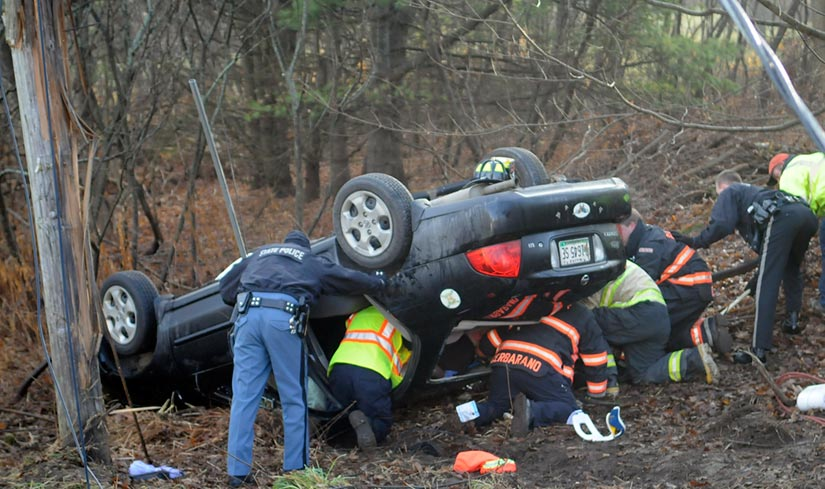 Staff photo by Andy Molloy ROLL OVER: Police and firefighters extricate a woman who was trapped in a car that rolled over this morning on the Hallowell Litchfield Road in West Gardiner. The vehicle left the road and snapped a utility pole around 8:30 a.m., according to Kennebec County Sheriff's Deputy Aaron Moody, pinning the driver for over half an hour. Several accidents were reported across Kennebec County, police said, as drivers encountered icy road conditions during the morning commute. The driver was flown to a trauma center for evaluation, Moody said.