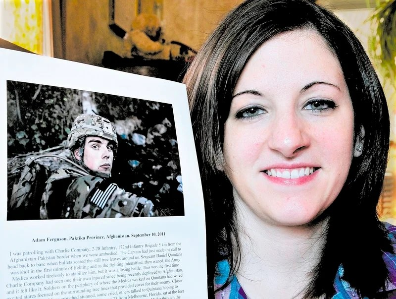 Brittany Miller poses with a Time magazine photograph of her husband, Michael, while he served in the U.S. Army in Afghanistan. It was chosen as one of Time's Top 10 Photos of 2011.