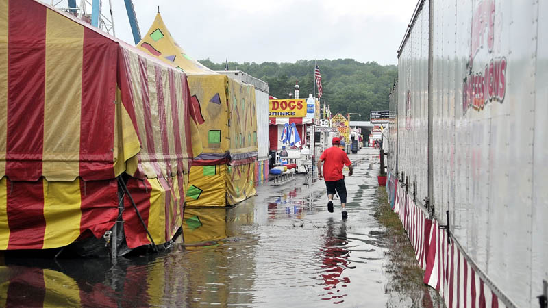 A fair worker triple jumps over a puddle t the Skowhegan State Fair friday morning.