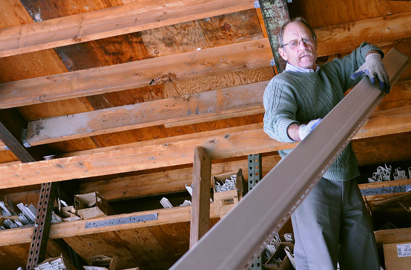 Kents Hill Lumber proprietor Stephen Monsulick hands a customer siding on Tuesday. The Readfield business is closing Nov. 3, after 36 years in business.