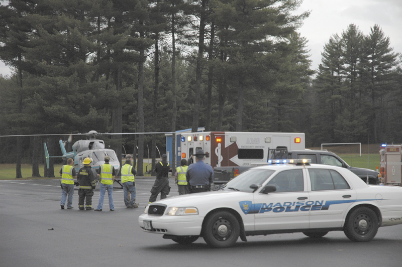"""A LifeFlight of Maine helicopter arrives Wednesday afternoon at a Madison High School parking lot to airlift Kerry Hebert, of Starks, to Central Maine Medical Center in Lewiston. Herbert was shot Wednesday in a possible """"hunting-related incident,"""" according to police."""