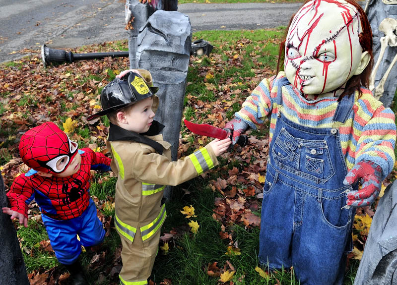 """Ben Coles, left, and Glen Carol cautiously check out the """"Chucky"""" character in the Halloween display at Melissa and Jeff Giguere's home in Waterville, on Wednesday. The kids were part of a large group from the Black Bear Nursery in Waterville."""
