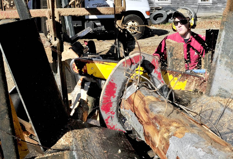 Jesse Bedard operates a firewood processor as a saw blade cuts through a full length log at Hawes & Son Logging and Excavation in Belgrade on Wednesday. After the wood is cut it is automatically split before a conveyor belt loads it into a delivery truck.