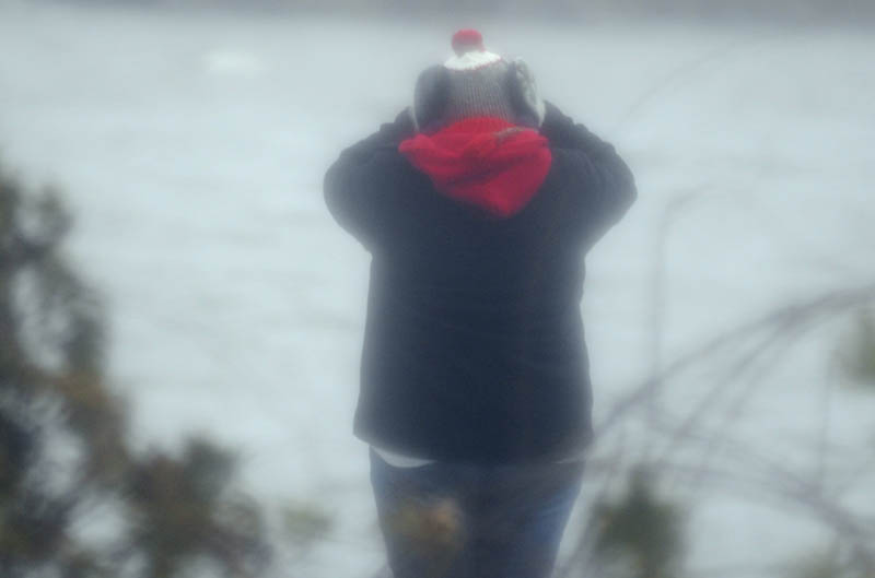 """Shannon Bubier covers her eyes Thursday while observing waves on Maranacook Lake in Winthrop. Gusts of wind up to 30 mph buffeted people across Maine as a nor'easter washed across the state. A self-described """"weather nut,"""" Bubier said the temperature was """"freezing"""" in the gusts coming across the lake."""