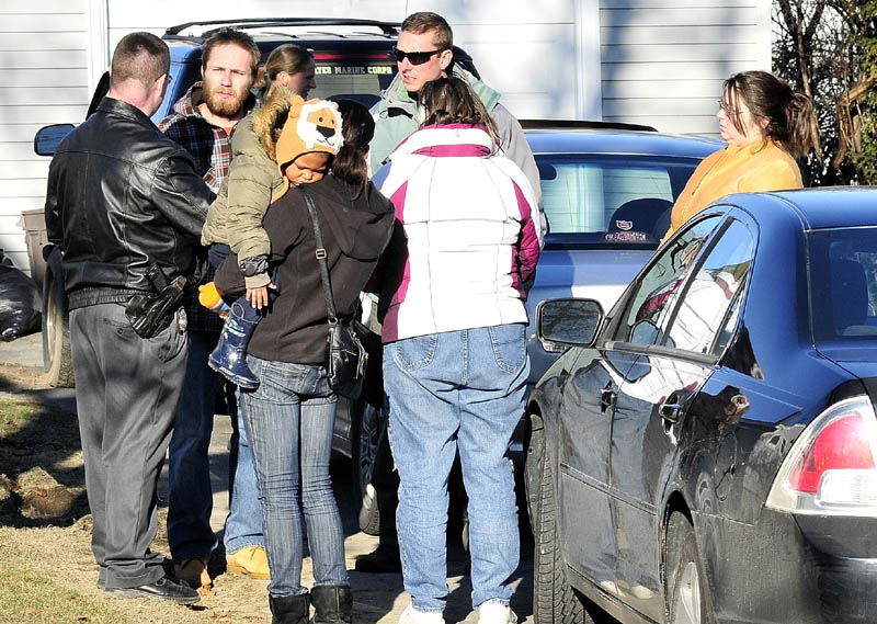 Maine State Police Detective Christopher Tupper, left, and Waterville Police Detective Lincoln Ryder, at right, speak with Justin DiPietro after he arrived at his home on Violette Avenue in Waterville on Dec. 18, 2011, as an extensive search was under way at his home and the neighborhood for his 20-month-old daughter, Ayla Reynolds, who has been missing since Dec. 17.