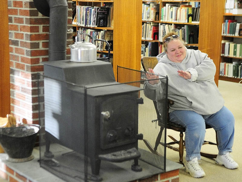 Denisa Laflamme, of Lewiston, warms up beside the wood stove at the Vassalboro Public Library Wednesday. The wood stove is part of the library's logo. Hours are Mondays and Wednesday from 12:30 to 8 p.m., and Saturday's from 10 a.m. to 6 p.m.