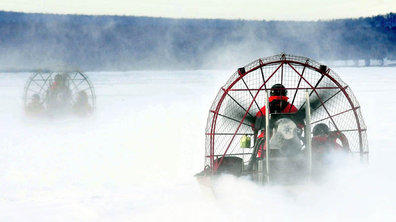 Two Maine Warden Service air boats head out on the ice on Rangeley Lake in Rangeley Jan. 1 to the location where snowmobiles went through the ice on Dec. 30. A warden service spokesman on Tuesday said plans to use a remote-controlled mini-submarine to locate three missing snowmobilers, presumed drowned in the lake, must wait for the ice to thicken.