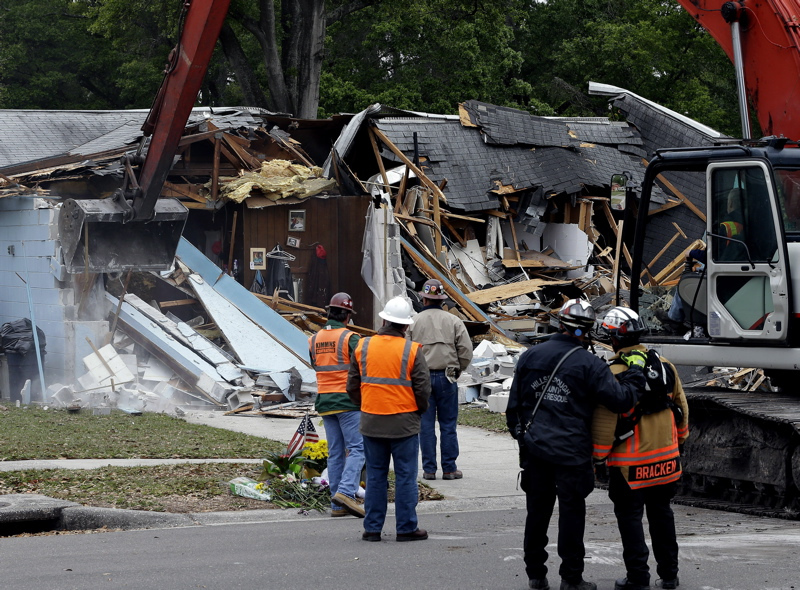 Demolition experts watch as the home of Jeff Bush, 37, is destroyed Sunday after a sinkhole opened up underneath it late Thursday evening swallowing Bush, 37, in Seffner, Fla.
