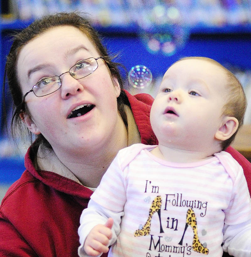 Crystal Callahan, left, and her daughter, Olivia Callahan, 9 months, watch bubbles during the Incredible Infants event on Friday in the Titcomb Children's Room at the Lithgow Library in Augusta. Every Friday from 10 to 10:30 a.m. library aide Jeanne Frost leads a program of songs and games for infants and their caregivers.