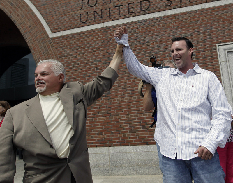 """Steve Davis, left, and Tommy Donahue clasp hands as they react outside federal court in Boston on June 12, 2012, after Catherine Greig, who spent 16 years on the run with former Boston mobster James """"Whitey"""" Bulger, was sentenced to eight years in prison for helping to hide one of the FBI's Ten Most Wanted Fugitives. Davis and Donahue are family members of victims."""
