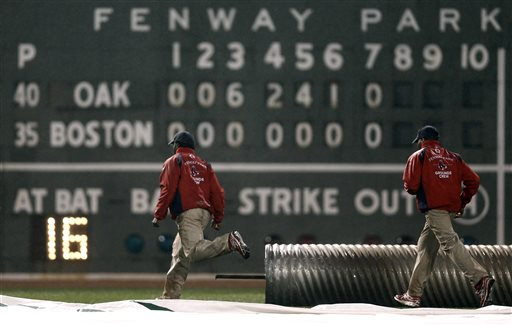 The grounds crew moves to cover the field after the seven inning of a baseball game between the Oakland Athletics and the Boston Red Sox at Fenway Park in Boston, Tuesday, April 23, 2013. (AP Photo/Winslow Townson)