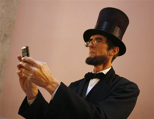 Robert Broski, a member of the Association of Lincoln Presenters, takes a photo with his cellphone during a visit to the Ohio Statehouse in Columus on Friday.