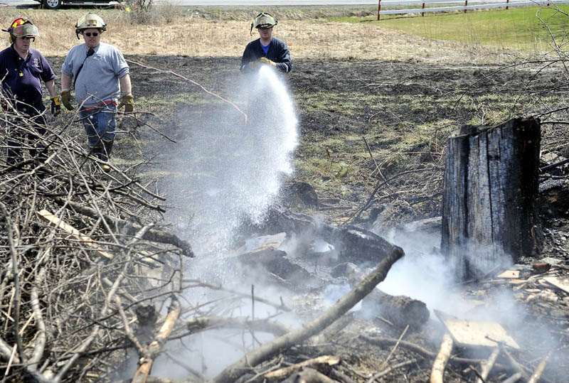 Randy Caswell, a volunteer firefighter with the Clinton Fire Department, sprays down the origin of a 5.4 acre grass fire at 434 Canaan Road in Clinton on Monday.