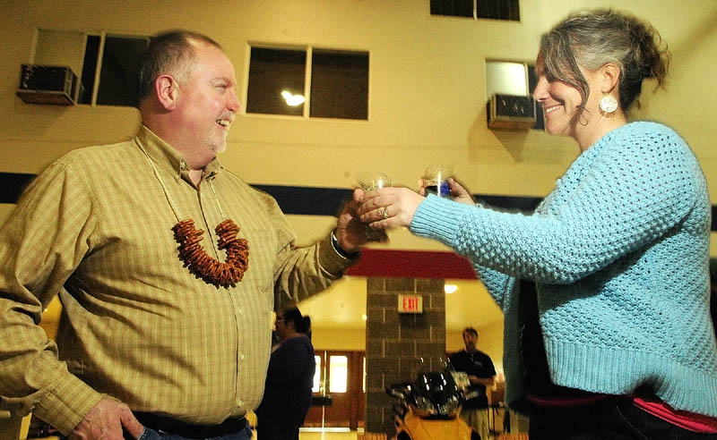 John Chapin, left, and Diana Chapin, of Montville, trade sample glasses of Allagash Black and Geary's Oakie Doakie Scotch Ale on Saturday during the Central Maine Brew Fest at the Augusta armory.